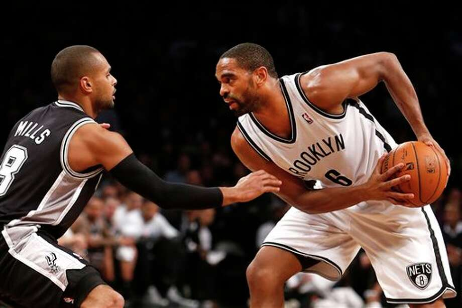 Brooklyn Nets' Alan Anderson (6) controls the ball against San Antonio Spurs' Patty Mills (8), of Australia, during the second half of an NBA basketball game on Thursday, Feb. 6, 2014, in New York. Brooklyn won 103-89. (AP Photo/Jason DeCrow) Photo: Jason DeCrow, AP / FR103966 AP