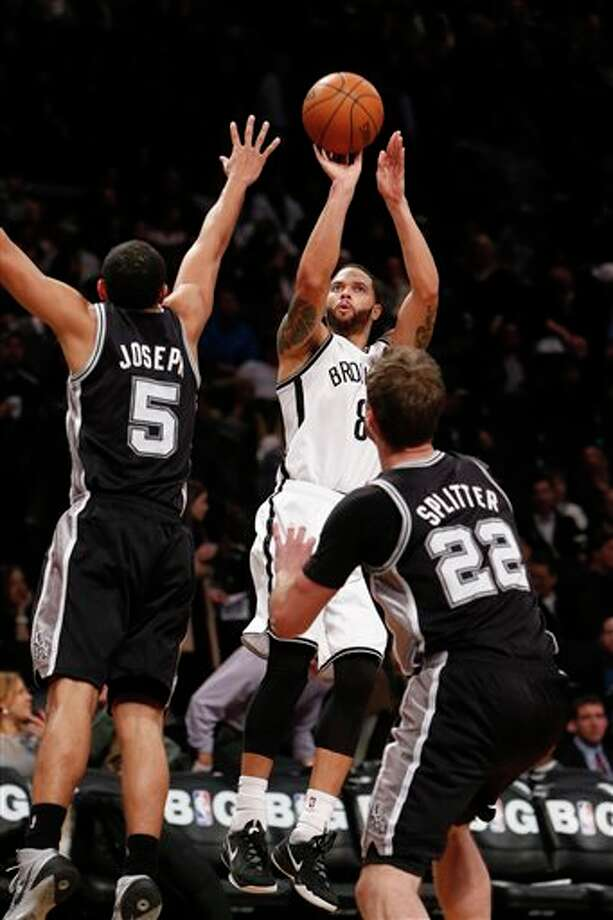 Brooklyn Nets' Deron Williams (8) shoots against San Antonio Spurs' Cory Joseph (5) and Tiago Splitter (22), of Brazil, during the second half of an NBA basketball game on Thursday, Feb. 6, 2014, in New York. Brooklyn won 103-89. (AP Photo/Jason DeCrow) Photo: Jason DeCrow, AP / FR103966 AP