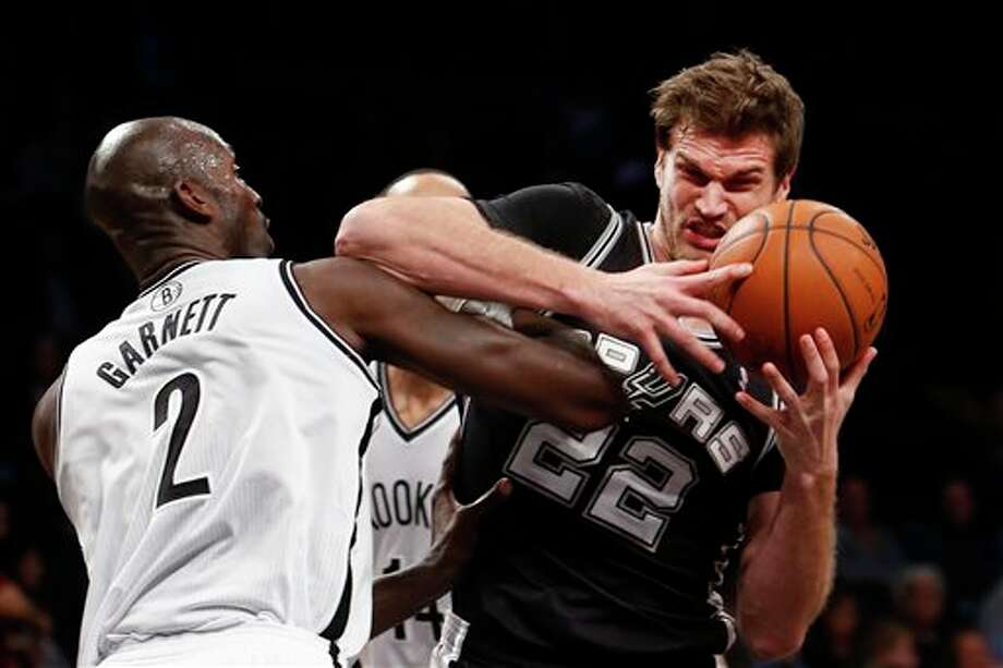 San Antonio Spurs' Tiago Splitter (22), of Brazil, is fouled by Brooklyn Nets' Kevin Garnett (2) during the first half of an NBA basketball game on Thursday, Feb. 6, 2014, in New York. (AP Photo/Jason DeCrow) Photo: Jason DeCrow, AP / FR103966 AP