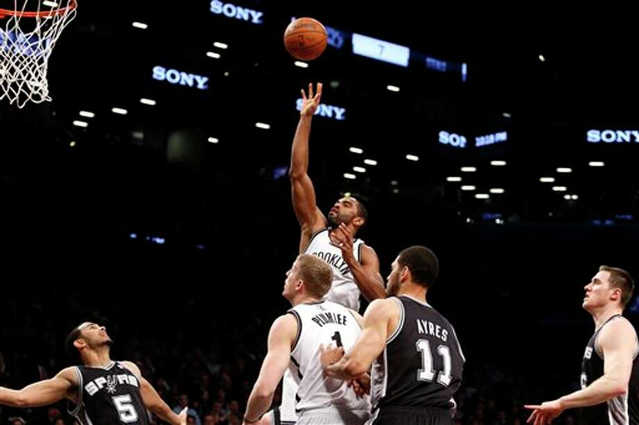 Brooklyn Nets' Alan Anderson, top center, shoots against the San Antonio Spurs during the second half of an NBA basketball game on Thursday, Feb. 6, 2014, in New York.  Brooklyn won 103-89. (AP Photo/Jason DeCrow) Photo: Jason DeCrow, AP / FR103966 AP
