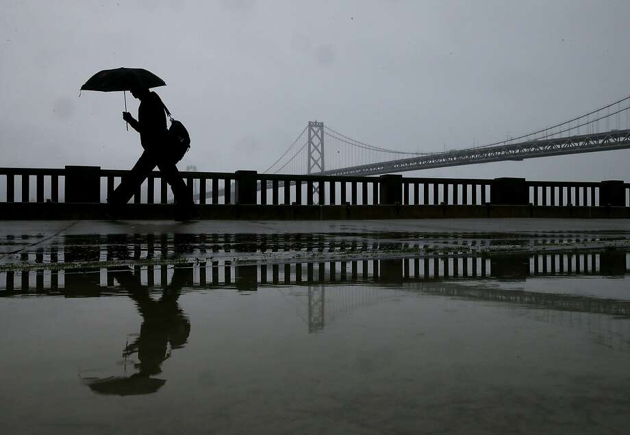 A pedestrian carries an umbrella while walking near the Bay Bridge Thursday in San Francisco. The Bay Area is getting much needed rain with up to a half inch of rain falling overnight and a bigger weather system expected to bring more precipitation over the weekend. Photo: Justin Sullivan, Getty Images