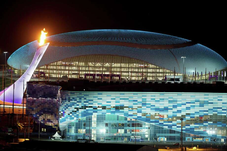 The Olympic Cauldron, left, is lit during a test between the Bolshoy Ice Dome, top, and the Iceberg Skating Palace, foreground, early Thursday morning, Feb. 6, 2014, in Sochi, Russia, prior to the start of the 2014 Winter Olympics. Photo: Pavel Golovkin, AP / AP