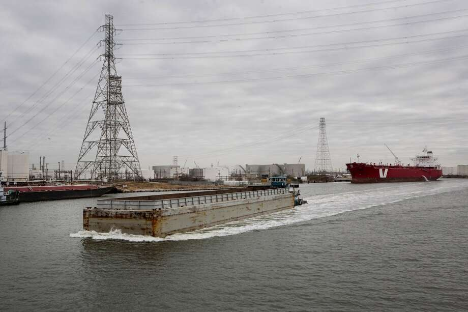 A barge moves along the Houston Ship Channel in Houston, Texas, U.S., on Thursday, Jan. 30, 2014. As record oil and gas output floods the country with cheap and abundant energy and brings the U.S. closer to energy independence, the bulk of the fuels get squeezed through Houston, the country's largest export gateway and the core of its biggest refining region. Photo: Scott Dalton, Bloomberg