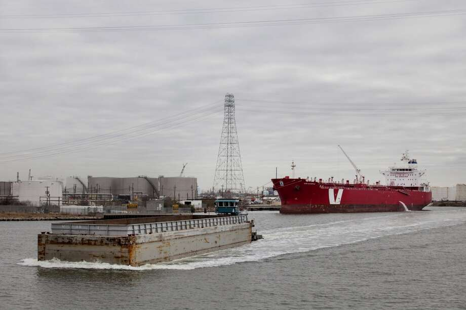 A towboat pushes a barge as a ship sits docked along the Houston Ship Channel in Houston, Texas, U.S., on Thursday, Jan. 30, 2014. As record oil and gas output floods the country with cheap and abundant energy and brings the U.S. closer to energy independence, the bulk of the fuels get squeezed through Houston, the country's largest export gateway and the core of its biggest refining region. Photo: Scott Dalton, Bloomberg