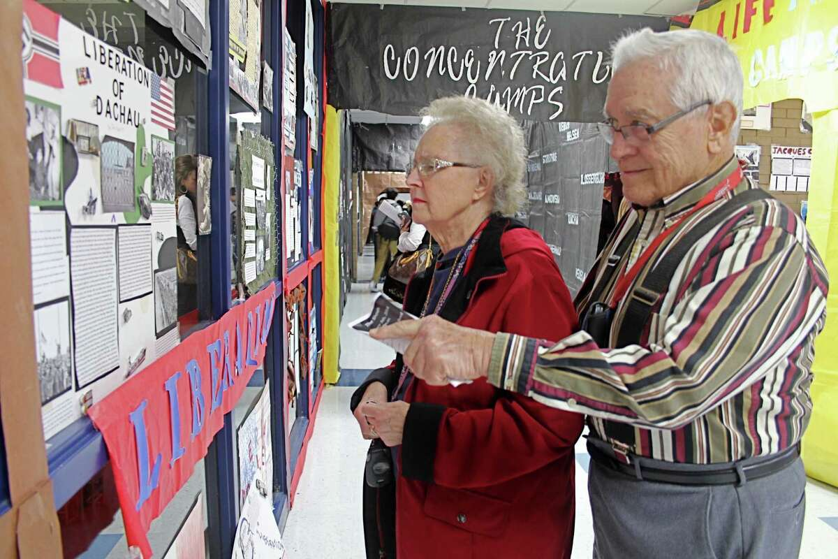 Thomas and Mary Jane Sullivan of Missouri City look at a poster of the Liberation of Dachau.
