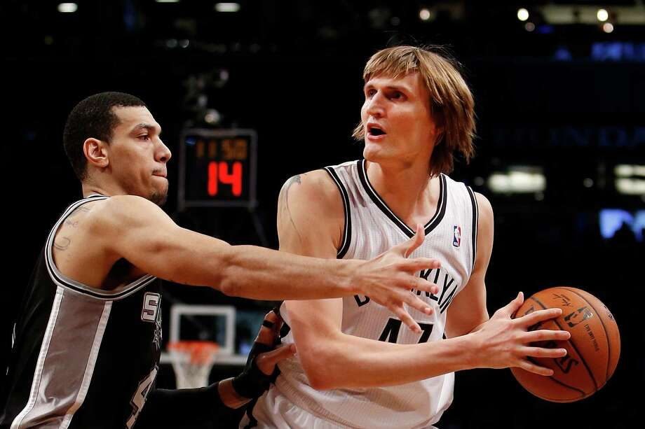 Brooklyn Nets' Andrei Kirilenko, right, of Russia, looks to pass away from San Antonio Spurs' Danny Green (4) during the second half of an NBA basketball game Thursday, Feb. 6, 2014, in New York.  Brooklyn won 103-89. (AP Photo/Jason DeCrow) Photo: Jason DeCrow, Associated Press / FR103966 AP
