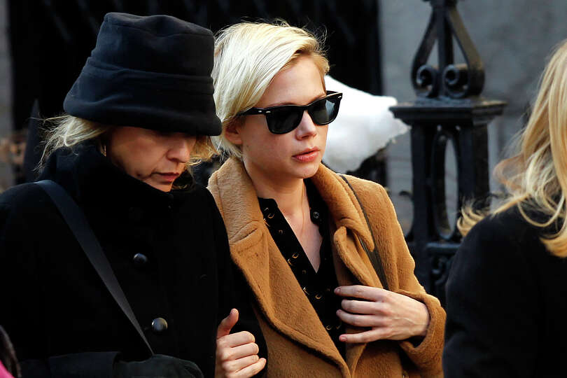 Actress Michelle Williams, right, arrives at the Church of St. Ignatius Loyola for the private fu