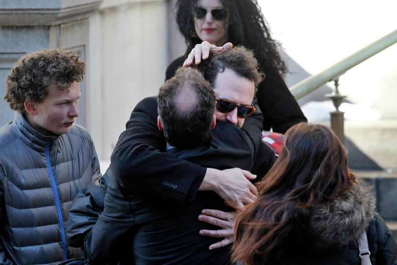 Writer David Bar Katz is embraced as he arrives at the Church of St. Ignatius Loyola for the private