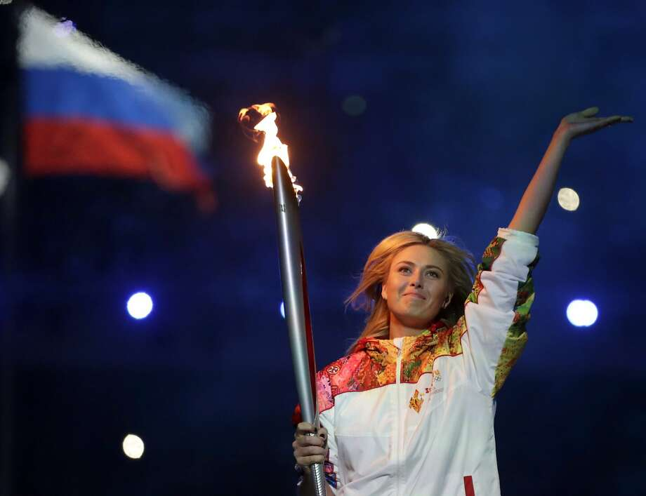 Russian tennis player Maria Sharapova carries the Olympic torch at the Opening Ceremony of the Sochi Games. Photo: Matt Dunham, Associated Press