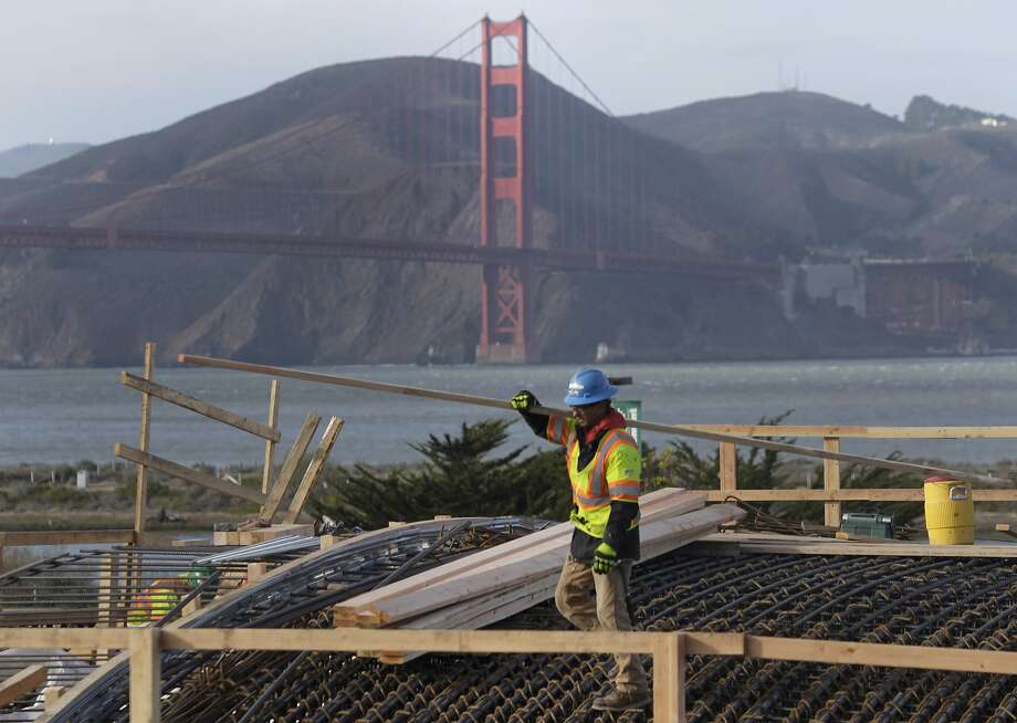 A construction worker carries building material on the roof of the Main Post tunnel for the Presidio Parkway project in San Francisco. Photo: Paul Chinn, The Chronicle