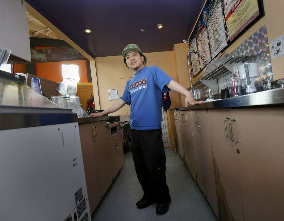 Jigmey Kunsang pauses in back of his counter at the gym where he makes protein shakes for customers Wednesday February 5, 2014 in San Francisco, Calif. Jigmey Kunsang works at a minimum wage job and finds it hard to make enough money at a cafe inside the Fitness SF off Brannan Street. Photo: Brant Ward, The Chronicle