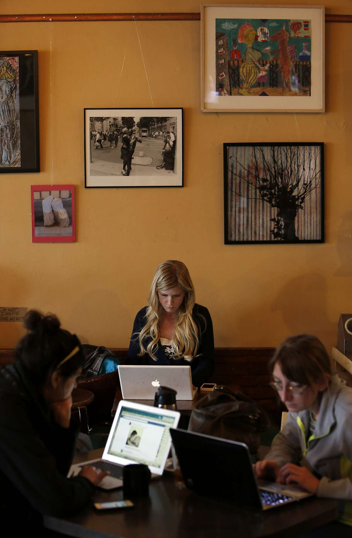 Customers use their laptops at Cafe Boheme on Tuesday, February 4, 2014. The Mission District in San Francisco, Calif., is facing a cultural and economic shift as new