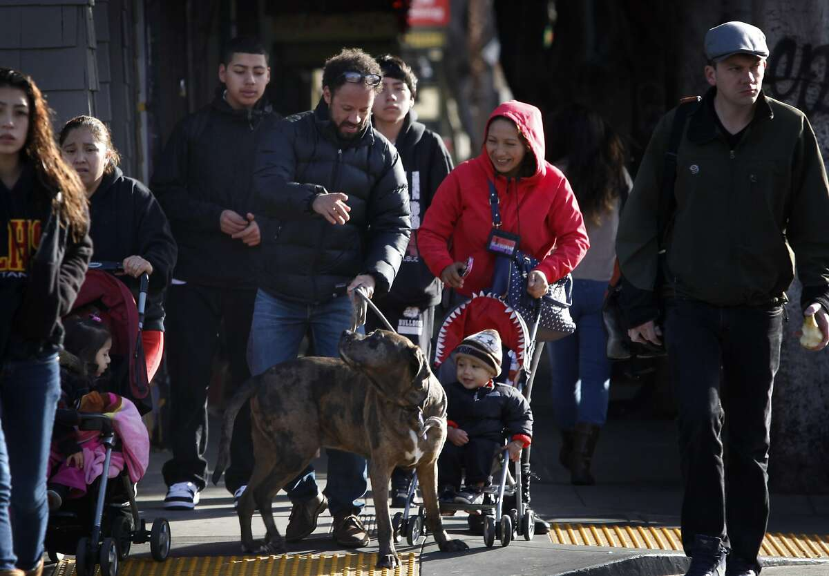 Long time resident Scott Briscoe (middle) crosses South Van Ness Ave. with his dog Cajun on 24th Street in San Francisco, Calif., on Wednesday, February 5, 2014.