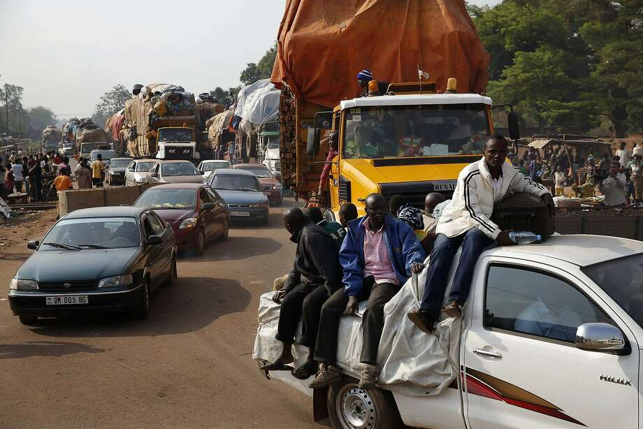 Thousands of Muslims flee Bangui using cars, pickups, trucks, and motorcycles, escorted by Chadian troops. Passengers faced jeering and stone-throwing. Photo: Jerome Delay, Associated Press