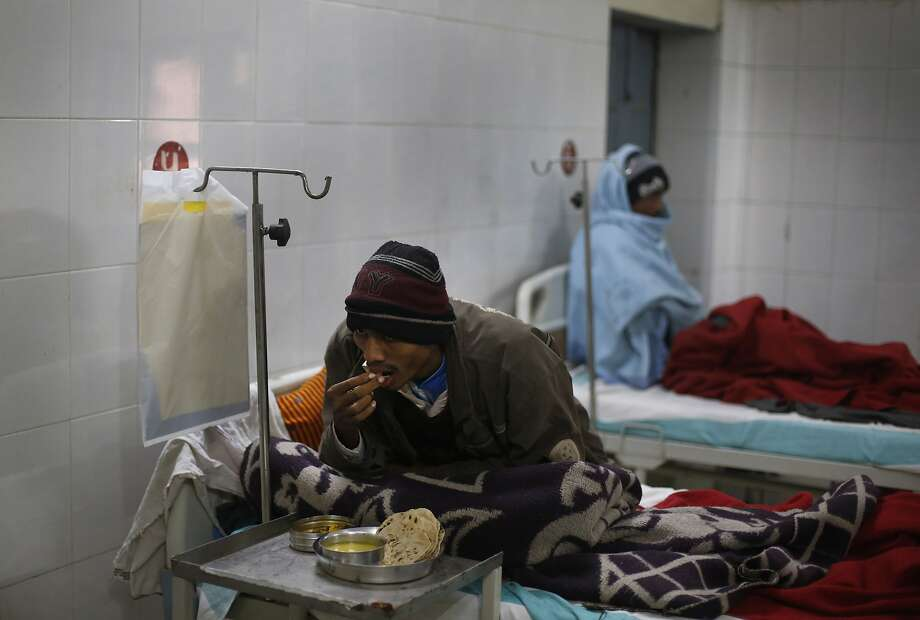 An unidentified patient suffering from tuberculosis eats his meal on a hospital bed in Varanasi. Photo: Rajesh Kumar Singh, Associated Press