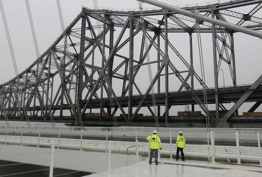 Caltrans officials check for water leakage along the steel safety barrier on the SAS bridge deck of the new eastern Bay Bridge span in San Francisco, Calif. on Thursday, Feb. 6, 2014. Engineers are monitoring areas where small amounts of water is seeping into the structure, a situation which is not uncommon, according to spokesman Andrew Gordon. Photo: Paul Chinn, The Chronicle
