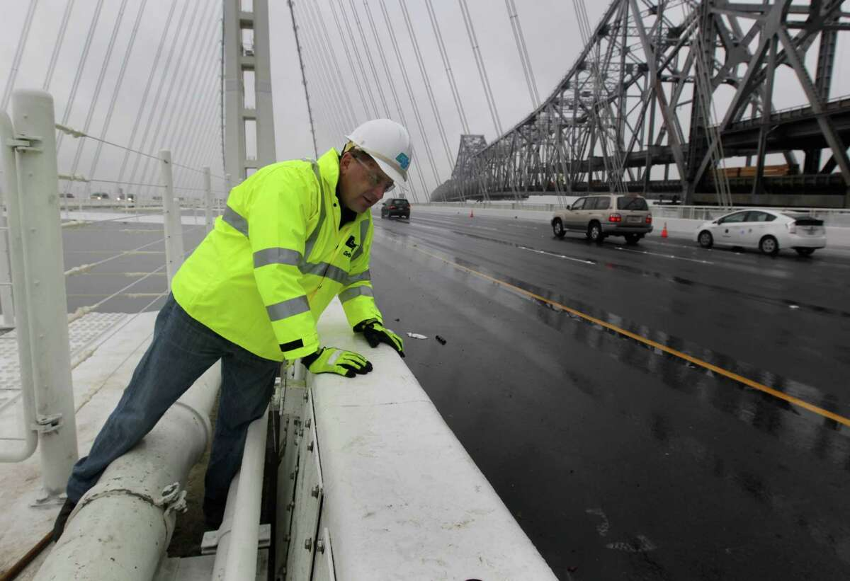 Caltrans engineer Bill Casey inspects for water leakage along the steel safety barrier on the deck of the new eastern Bay Bridge span.