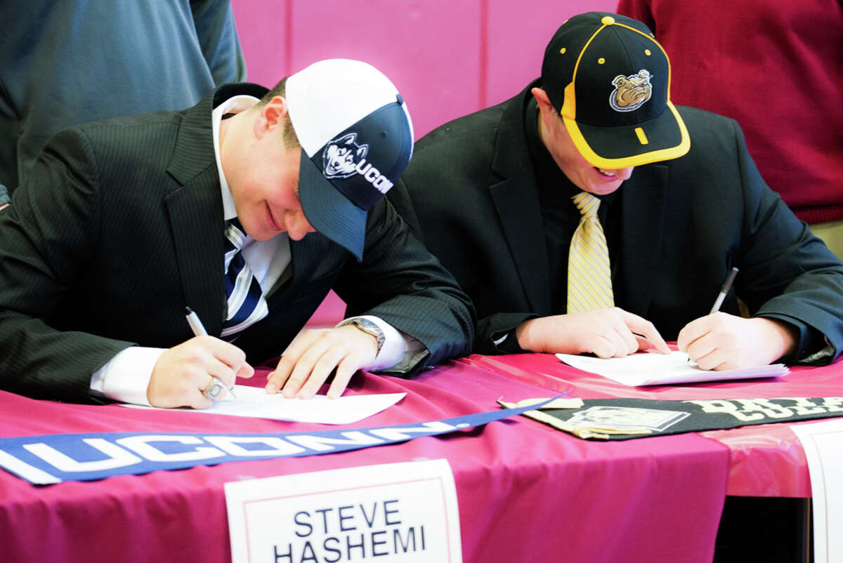 Steve Hashemi, left, and Peter Mestre signing their letters of intent. Hashemi will play football at UConn, Mestre at Byrant College.