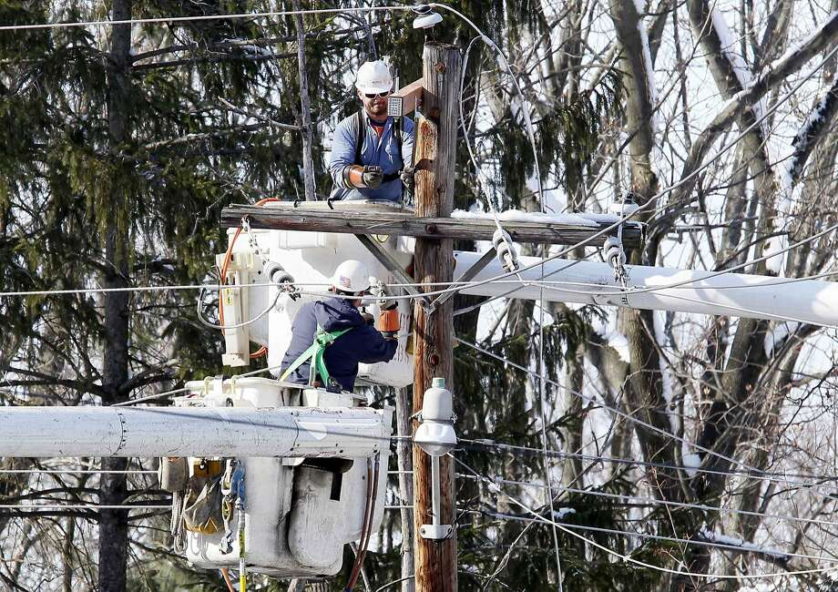 Philadelphia Electric Co. linesmen work to restore electricity by replacing broken power lines in Upper Dublin Township. Photo: Tom Mihalek, Reuters