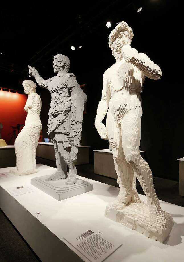 """David,"" (R) a Nathan Sawaya sculpture, is displayed with others in the 'Art of the Brick' show at Discovery Times Square on June 18, 2013 in New York City.  Sawaya created the pieces entirely with LEGO toy bricks and the exhibition features over 100 works of art created from millions of the toy bricks. Many pieces mimic famous works of art. Photo: Mario Tama, Getty Images / 2013 Getty Images"