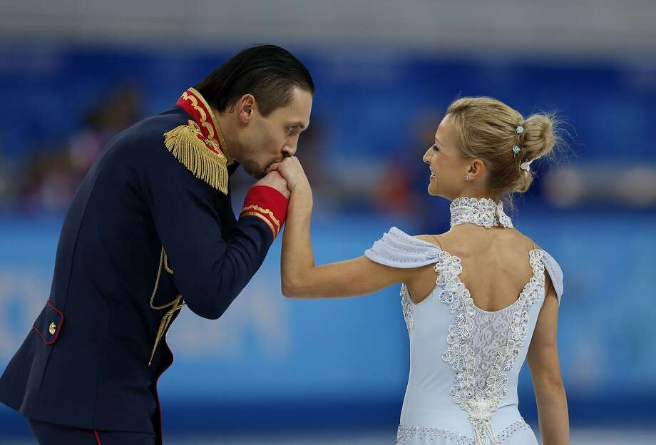 An officer and a gentleman: Russia's Maxim Trankov kisses the hand of partner Tatiana Volosozhar after performing their Figure Skating Pairs Team Short Program at Sochi Winter Olympics. Photo: Adrian Dennis, AFP/Getty Images