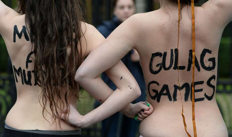 "A Putin putdown: Two topless Femen activists decry the Sochi ""Gulag Games"" in front of the Russian Embassy in Berlin. Femen staged the protest on the opening day of the Olympics to demonstrate against President Vladimir Putin's ""dictatorship and oppression of human rights."" Photo: Patrik Stollarz, AFP/Getty Images"