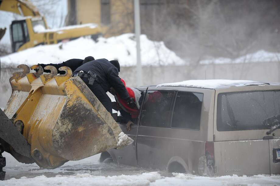 Scoopy duo:A pair of Detroit cops use the scoop of a front-end loader to rescue two people stranded in a minivan during street flooding caused by a water main break in Motown. Photo: David Coates, Associated Press
