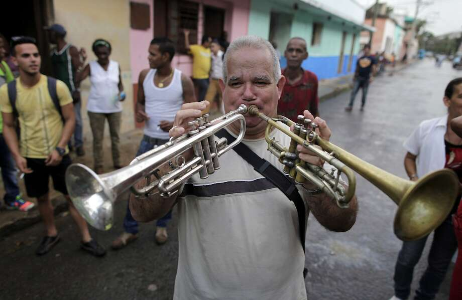Let's play two: Carlos Pineiro doubles up on the trumpet during the celebration of a mock funeral known as the Burial of Pachencho in Santiago de Las Vegas, Cuba. The tradition was began in 1984, when villagers got the idea of staging a fake burial to mark the end of local carnival season. Photo: Franklin Reyes, Associated Press