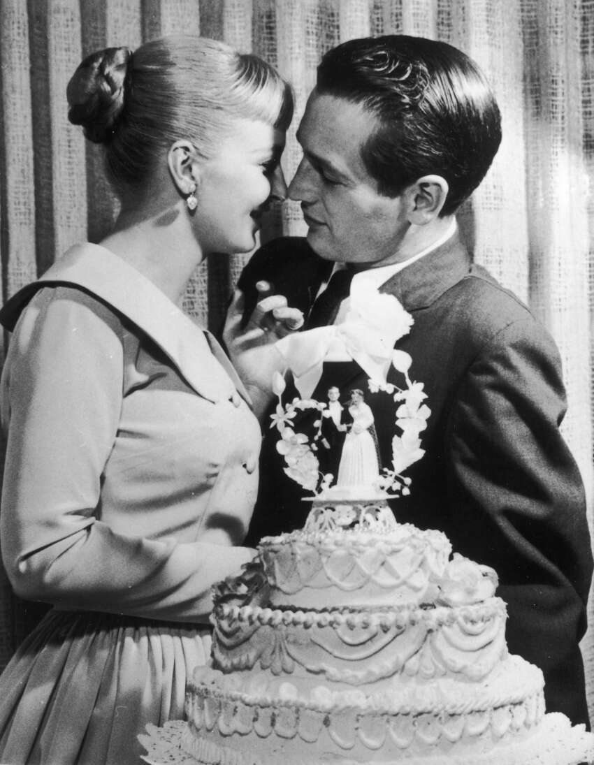 American actors and newlyweds Paul Newman and Joanne Woodward kiss behind a wedding cake during their wedding reception at the El Rancho hotel-casino, Las Vegas, Nevada, January 29, 1958.
