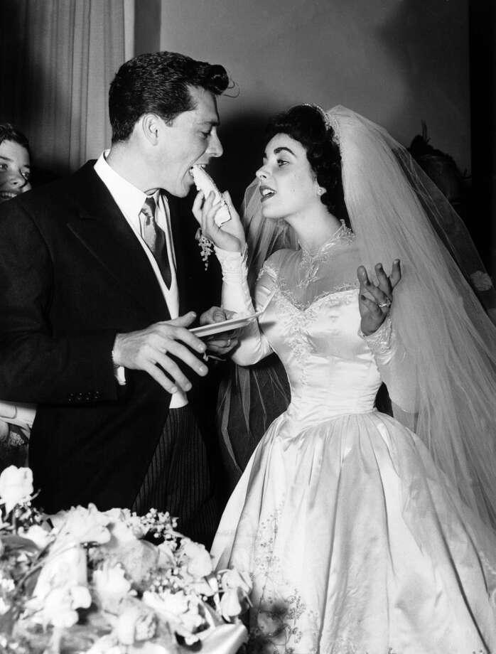 Elizabeth Taylor serves her new husband Conrad Hilton Jr cake during their wedding reception on June 5, 1960 in Los Angeles. Photo: Keystone-France, Gamma-Keystone Via Getty Images