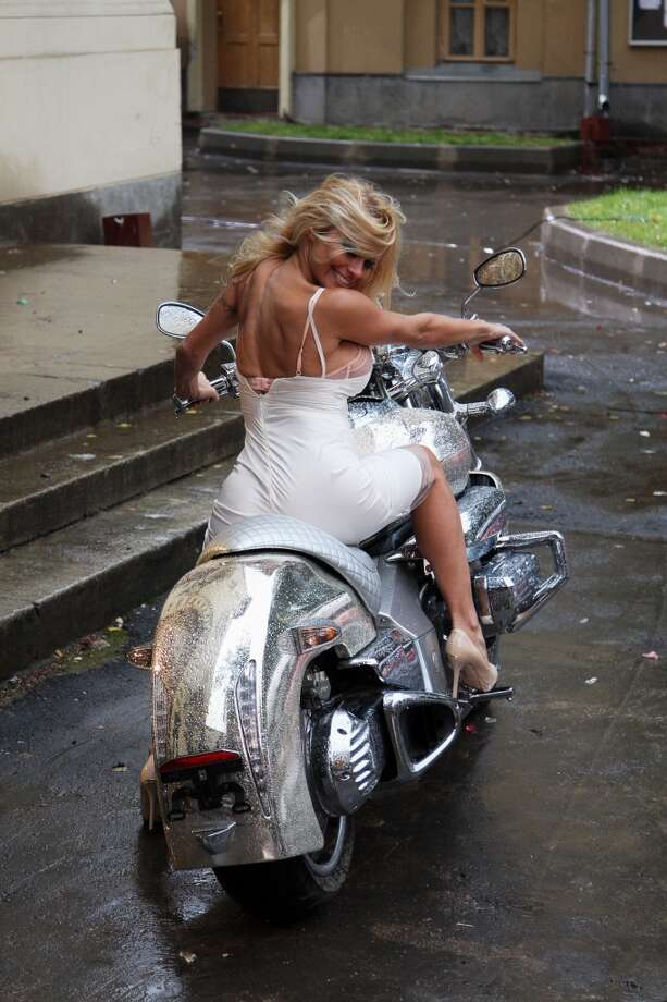"""Pamela Anderson, dressed as a bride, rides a motobike whilst shooting a music video for """"Piligrim"""" on September 12,  2008, in  Moscow, Russia. Anderson was paid $200,000 for appearing in the band's video for their track """"Rave of Motors."""" Photo: Epsilon, WireImage"""