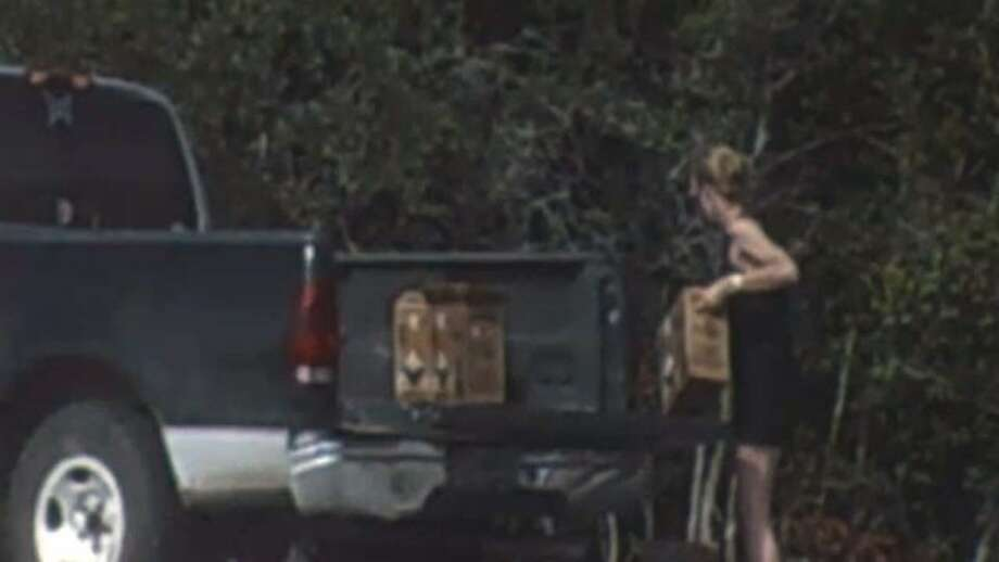 A Fort Bend County surveillance camera captured this image of a woman unloading boxes at an illegal dump site on July 20, 2011.