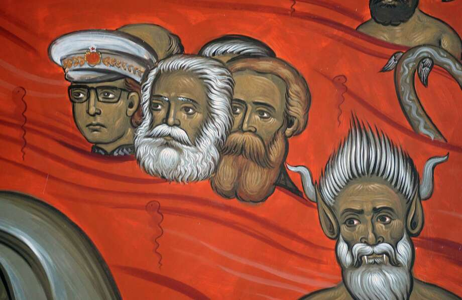 This photo taken Tuesday, Feb. 4, 2014 shows the brightly-colored newly painted fresco in the Serbian Orthodox Church of Christ's Resurrection in Montenegro's capital Podgorica. The fresco allegedly shows late Yugoslav autocratic leader Josip Broz Tito drowning in red fiery waves of hell with Karl Marx and Friedrich Engels, authors of the 1848 Communist Manifesto. They are in the company of Adam and Eve, together with some of Montenegro's current politicians and people wearing Muslim turbans. What appear to be rival church priests are being swallowed through a huge jaw of an angry gray beast with pointed devil ears. The fresco has triggered much attention and public controversy in this tiny former communist country. (AP Photo/Risto Bozovic) Photo: Risto Bozovic, STR / AP