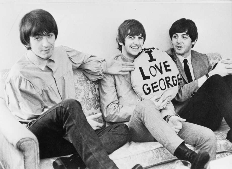 Three of the four members of the British rock group The Beatles sit on a sofa. L-R: George Harrison (1943 - 2001), Ringo Starr and Paul McCartney. Starr holds a pillow, which has been lettered, 'I LOVE GEORGE.'  (Photo by Express/Express/Getty Images) Photo: Express, Getty Images