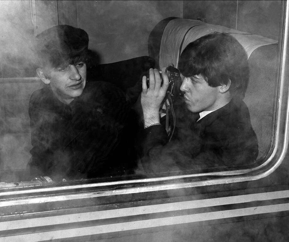 The Beatles 1964 US Tour, Paul McCartney of British pop group The Beatles photographs drummer Ringo Starr as they sit in their carriage on board the train from New York to Washington DC during the band's tour of the States  (Photo by Popperfoto/Getty Images) Photo: Popperfoto, Popperfoto/Getty Images / Popperfoto
