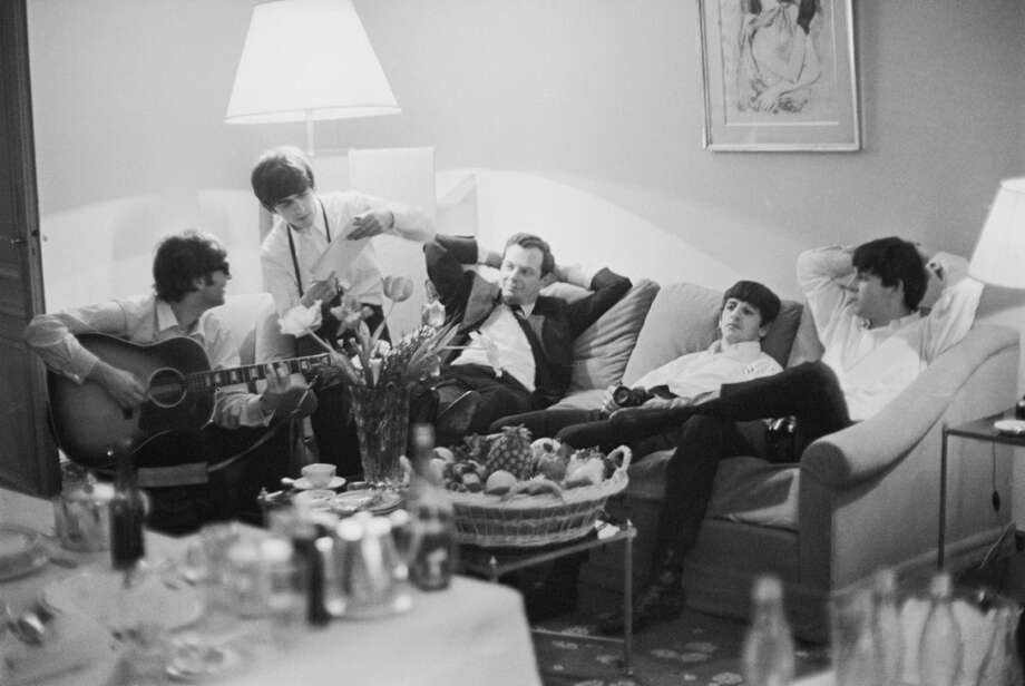The Beatles relax in a hotel room in Paris, 16th January 1964. From left to right, John Lennon (1940 - 1980), George Harrison (1943 - 2001), band manager Brian Epstein (1934 - 1967), Ringo Starr and Paul McCartney. (Photo by Harry Benson/Express/Hulton Archive/Getty Images) Photo: Harry Benson, Getty Images