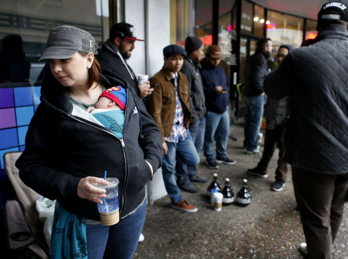 Sarah Barnes keeps her 2 month-old baby son Michael warm as she waits in line outside for hours to taste the Russian River Brewing Company's much-anticipated Pliny the Younger Ale, Friday February 7, 2014, in Santa Rosa, Calif.