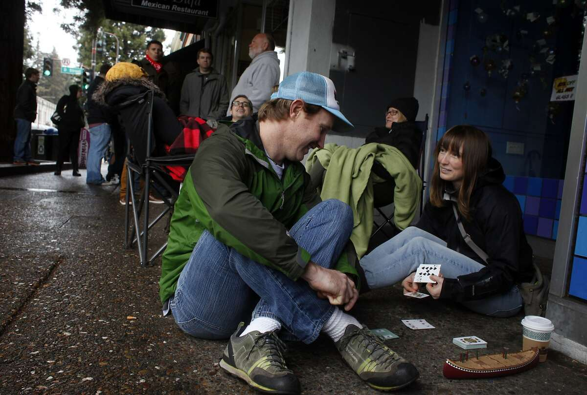 Mike Bartlett and Shannon Vincent from Bellingham, Washington play cribbage as they wait in line outside since 6:30 in the morning to be some of the first to taste Russian River Brewing Company's much-anticipated Pliny the Younger ale, Friday February 7, 2014, in Santa Rosa, Calif.
