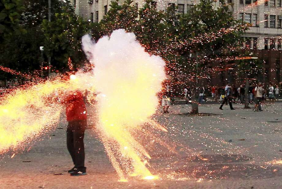 Bomb explodes on cameraman: Santiago Andrade, a cameraman for the Bandeirantes network, is hit in the head with some kind of explosive device during clashes between demonstrators and police in Rio de Janeiro. Andrade was seriously injured and underwent surgery. Photo: Domingos Peixoto, AFP/Getty Images
