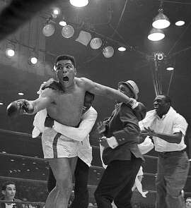 ** FILE ** Cassius Clay's handlers hold him back as he reacts after he is announced the new heavyweight champion of the world on a seventh round TKO against Sonny Liston in Miami Beach, Fla., on Feb. 25, 1964. It will be 40 years ago Wednesday, Feb. 25, 2004 that Ali won the heavyweight title. The once brash, mouthy young champion now trembles with age and disease and talks sparingly in whispers. But the memories are fresh for Gene Kilroy, who was at Ali's side for much of his career as his trusted confidante and pal. (AP Photo)  Muhammad Ali, then known as Cassius Clay, reacted after his seventh-round TKO against Sonny Liston on Feb. 25, 1964.     Muhammad Ali, then known as Cassius Clay, reacted after his seventh-round TKO against Sonny Liston on Feb. 25, 1964.