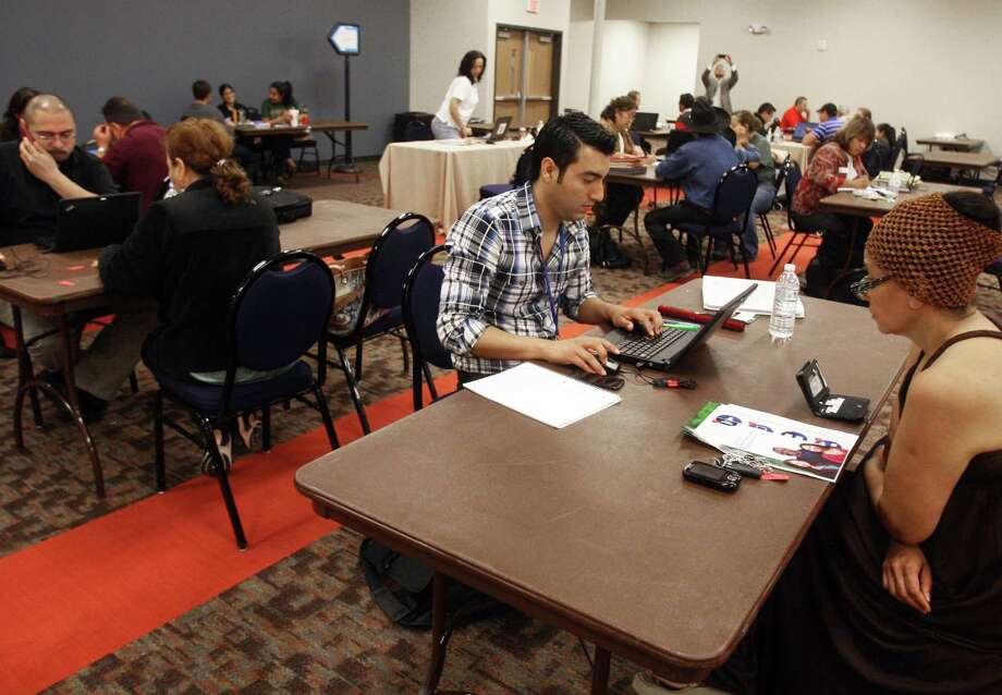 Ruben De La Rosa, center, assist attendees sign up for ACA during an Affordable Care Act enrollment fair held at the University of Texas-Pan American's CESS building saturday, Feb. 1, 2014 in Edinburg, Texas.(AP Photo/The Monitor, Joel Martinez) Photo: Joel Martnez, MBO / The Monitor
