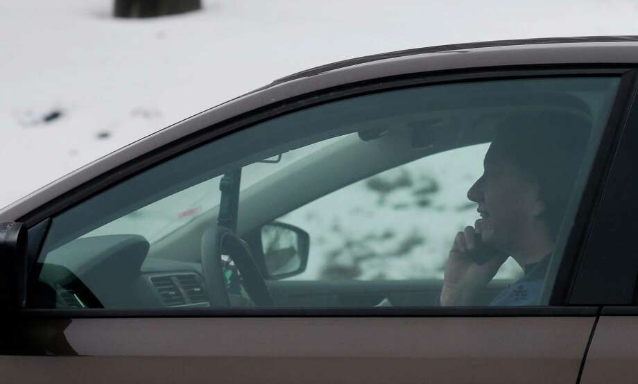 FILE -  In this Dec. 19, 2013 photo, a motorist talks on a cell phone while driving on an expressway in Chicago.  A sophisticated, real-world study confirms that dialing, texting or reaching for a cellphone while driving raises the risk of a crash or near-miss, especially for younger drivers. But the research also states that simply talking on the phone did not prove dangerous, as it has in other studies. (AP Photo/Nam Y. Huh) Photo: Nam Y. Huh, STF / AP