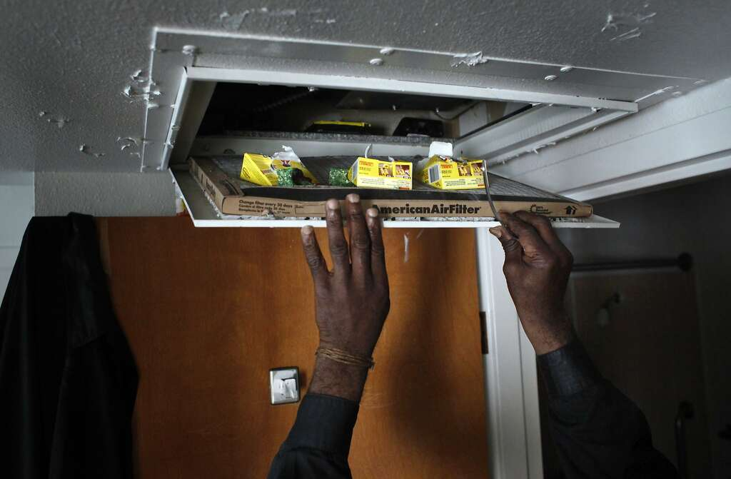 Eddie Williams, 62 years old, puts mice bait inside his air vents in the ceiling of his apartment. Photo: Lacy Atkins, The Chronicle