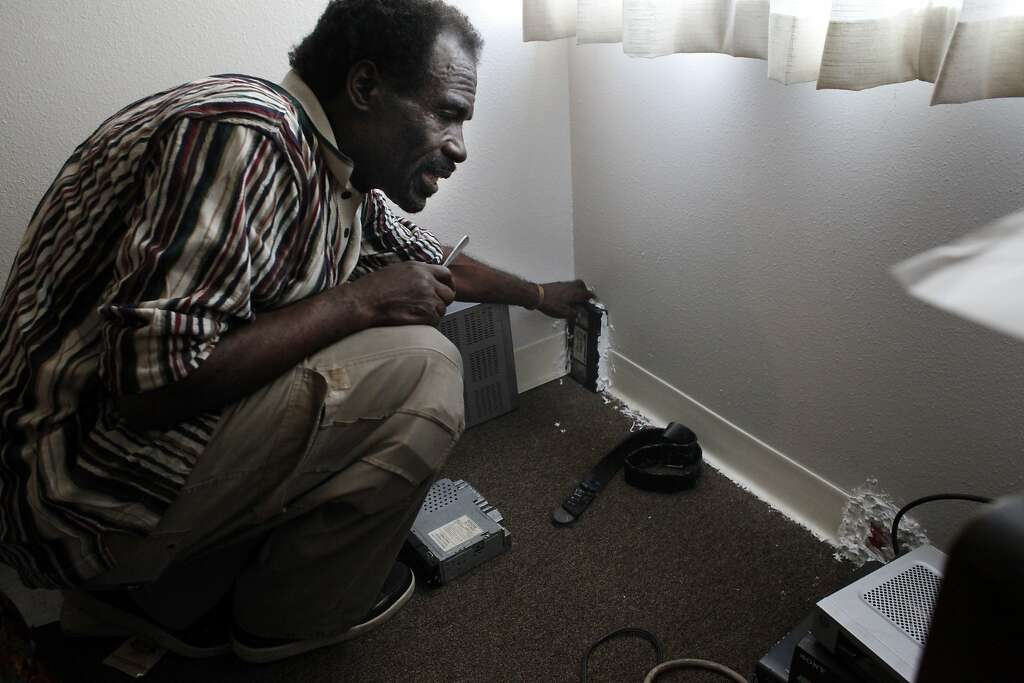 Eddie Williams, 62,  places video cassettes, china plates and wooden boxes glued to the walls to sto. Photo: Lacy Atkins, The Chronicle