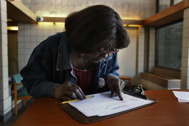 Helen Hall, 81, checks the sign in sheet at the front deck of Nevin Plaza public housing complex, Friday November 1, 2013, in Richmond, Calif.  In her 17 years living in Nevin, Hall has seen the place overrun by drug dealers and prostitutes who roam the halls and sneak into the building with impunity. Hall says sheÕs all thatÕs keeping her home from turning completely into a Òdrug den.Ó ÒIf I give it up, then itÕll really turn into something bad,Ó she said. ÒAnd these old folks need a place. They donÕt got nowhere else to go.Ó Photo: Lacy Atkins, The Chronicle