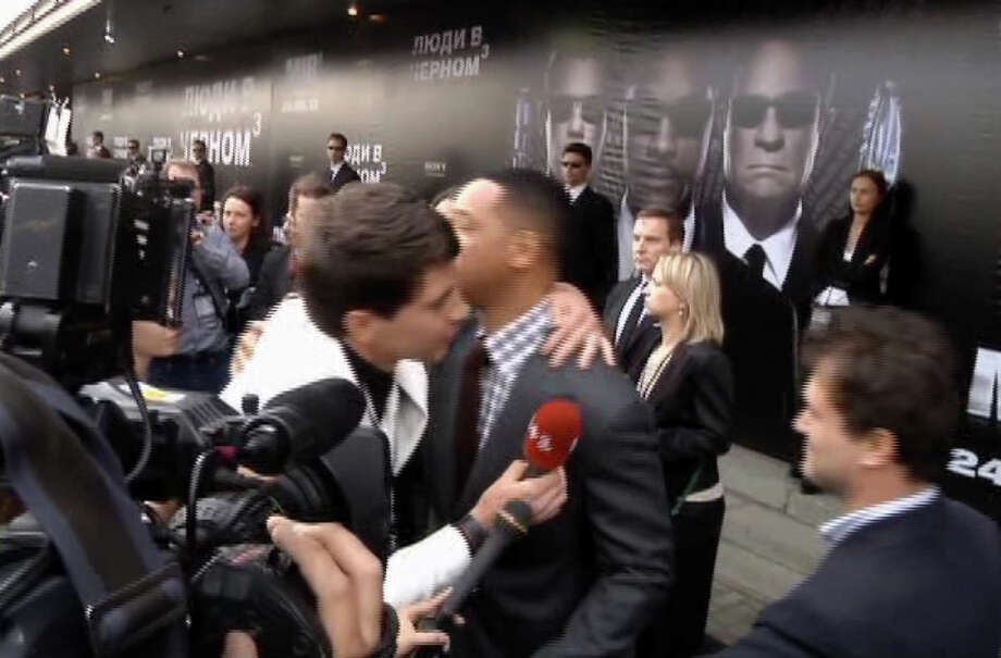"In this video image taken from AP video U.S. actor Will Smith, center right, is embraced by reporter Vitalii Sediuk, white suit, from the Ukrainian television channel 1+1  on the red carpet before the premiere of ""Men in Black III"" Friday May 18, 2012 in Moscow. Photo: Associated Press / APTN"