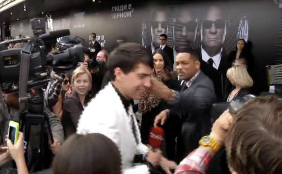 "In this video image taken from AP video U.S. actor Will Smith, center right, slaps reporter Vitalii Sediuk, white suit, from the Ukrainian television channel 1+1  on the red carpet before the premiere of ""Men in Black III"" Friday May 18, 2012 in Moscow. Photo: Associated Press / APTN"