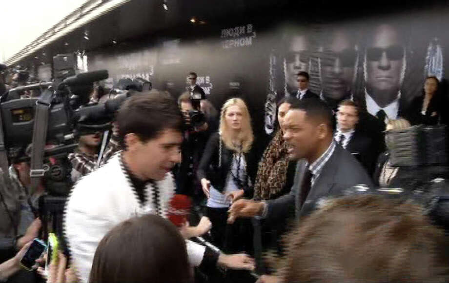 "In this video image taken from AP video U.S. actor Will Smith, center right, reacts after he was embraced by reporter Vitalii Sediuk, white suit, from the Ukrainian television channel 1+1  on the red carpet before the premiere of ""Men in Black III"" Friday May 18, 2012 in Moscow. Photo: Associated Press / APTN"