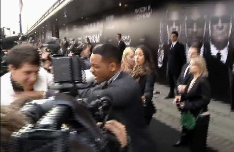 "In this video image taken from AP video U.S. actor Will Smith, center, pushes reporter Vitalii Sediuk, white suit, from the Ukrainian television channel 1+1  on the red carpet before the premiere of ""Men in Black III"" Friday May 18, 2012 in Moscow. Photo: Associated Press / APTN"