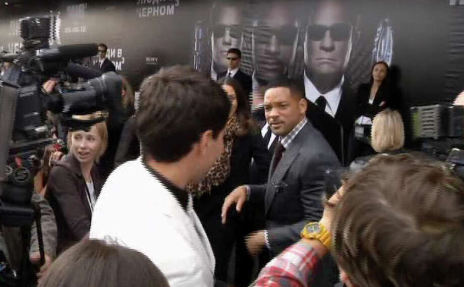 "In this video image taken from AP video U.S. actor Will Smith, center right, walks away from reporter Vitalii Sediuk, white suit, from the Ukrainian television channel 1+1 after slapping him on the red carpet before the premiere of ""Men in Black III"" Friday May 18, 2012 in Moscow. Photo: Associated Press / APTN"